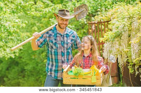 Inspect your garden daily to spot insect trouble early. Family dad and daughter little girl planting plants. Day at farm. Planting flowers. Plant veggies. Planting season. Popular in garden care stock photo