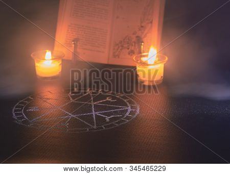 spell book with two candles on the sides and a pentacle drawn on a black background and some mysterious smoke stock photo
