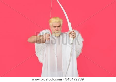 God of love. February 14. Cupid angel with bow and arrows. Symbol of love. Happy Valentines Day. Serious man in angel costume. Valentines day angel. Cupid. Amour. Cupid with bow. Cupid shoot with bow stock photo