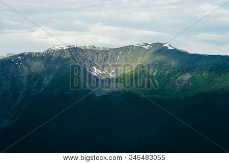 Atmospheric alpine landscape to giant mountain range. Snow on high rocky ridges. Forest on massive slopes. Tranquil atmosphere. Shadows of clouds on big mountains. Majestic scenery on high altitude. stock photo