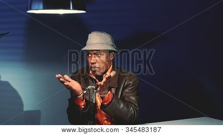 Young black man in handcuffs refusing accusation in his address during police interview in interrogation room. stock photo