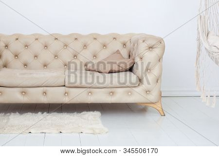 Interior of modern minimalist living room with comfortable beige sofa, hammock and fluffy carpet. Spacious room interior with comfortable sofa near white wall. Home decor, furniture. Scandinavian stock photo