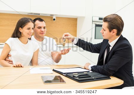 real estate agent is selling an apartment to a young family. conclusion of a lease and purchase of a house, apartment. man shows housing stock photo