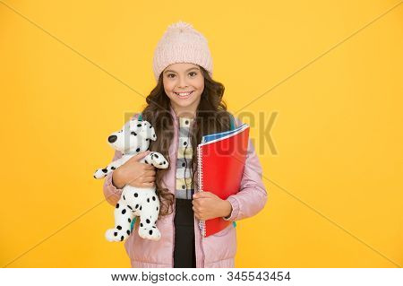 Care and treatment of animals. Studying veterinary medicine. Happy child hold toy dog and books. Little girl smile with soft toy. School classes. Toy dog. Learn and play. School and education. stock photo