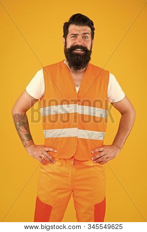 Its time to work a harder. Happy hipster on yellow background. Bearded hipster smiling in work clothes. Hipster construction worker with long beard and mustache. Builder or miner in hipster style. stock photo