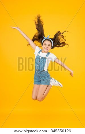 Energy inside. Small girl jump yellow background. Enjoy freedom. Childrens day concept. Spirit of freedom. Active girl feel freedom. Feeling free. Carefree kid. Summer holidays. Jump of happiness. stock photo