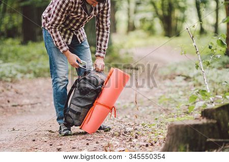 Hiker holding his camping backpack. traveler opening backpack while traveling in beautiful wood. Theme hiking and travel. Man traveling in forest with backpack. Active healthy man hiking in forest stock photo