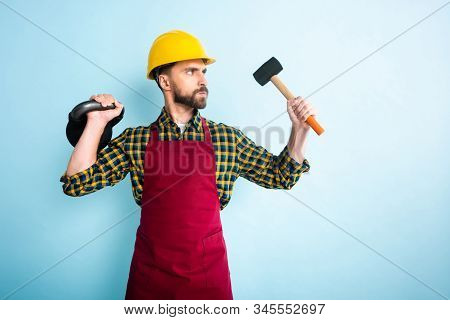 angry bearded workman in safety helmet holding hammer and dumbbell on blue stock photo
