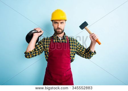 angry bearded workman holding hammer and dumbbell on blue stock photo