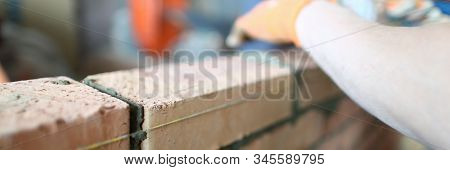 Close-up of skilled builder wearing special gloves to protect arms. Experienced constructor with hammer to lay red bricks and make big masonry perfect. Building concept stock photo