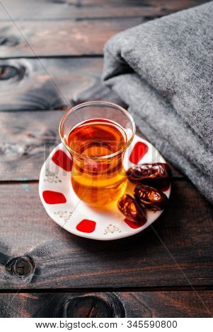A glass of black tea and dates on a saucer with a folded blanket on the background stock photo
