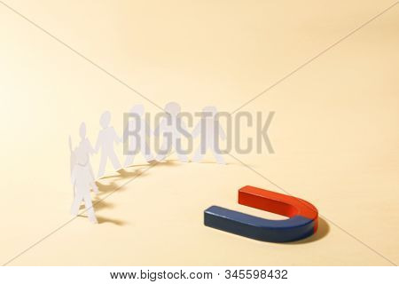 Magnet attracting paper people on beige background stock photo