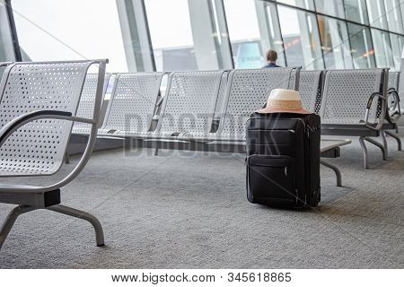 Suitcase in an airport waiting area, concept of lost luggage, one black suitcase in an airport waiting room. stock photo