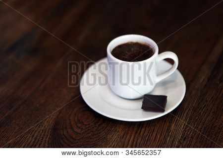 cup of hot coffee on a dark background. Hot Chocolate in a white ceramic mug. teacup with hot chocolate. tasty drink on porcelain mug. A Cup of festive hot chocolate. stock photo
