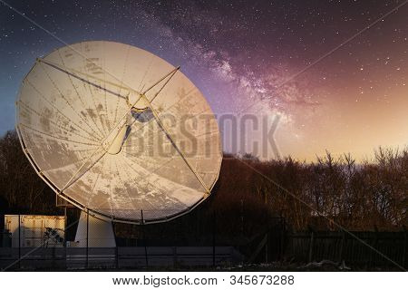 Satellite dish large and antenna for communication and mobile technology network at night starry sky showing the galaxy stars stock photo
