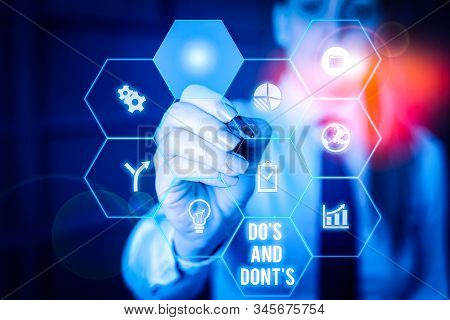 Word writing text Do S And Don tS. Business concept for Rules or customs concerning some activity or actions Woman wear formal work suit present presentation using smart latest device. stock photo