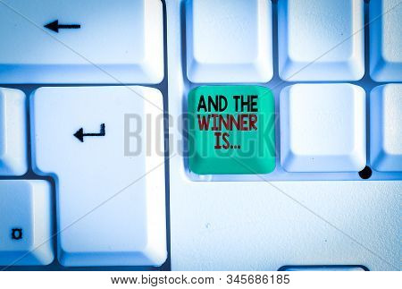 Word writing text And The Winner Is. Business concept for announcing a demonstrating or thing that wins something White pc keyboard with empty note paper above white background key copy space. stock photo