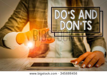 Writing note showing Do S And Don tS. Business photo showcasing Rules or customs concerning some activity or actions Business woman sitting with mobile phone on the table. stock photo