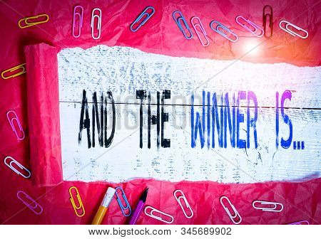 Handwriting text writing And The Winner Is. Concept meaning announcing a demonstrating or thing that wins something Stationary and torn cardboard placed above a wooden classic table backdrop. stock photo