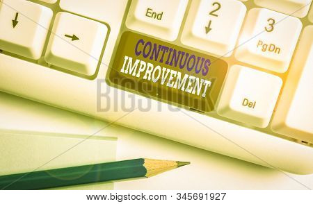 Conceptual hand writing showing Continuous Improvement. Business photo text ongoing effort to improve products or processes White pc keyboard with note paper above the white background. stock photo