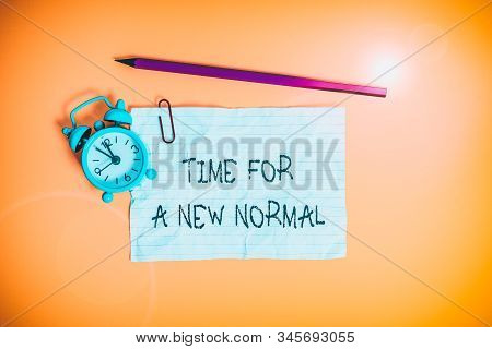 Conceptual hand writing showing Time For A New Normal. Business photo showcasing Make a big dramatic change Replace the expected Metal alarm clock ccrushed sheet pencil colored background. stock photo
