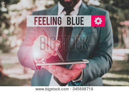 Text sign showing Feeling Blue. Conceptual photo Feeling of desperation because of sadness or missing someone Businessman in blue suite stands with mobile phone in hands. stock photo
