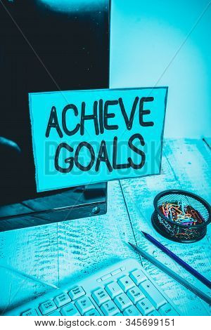 Conceptual hand writing showing Achieve Goals. Business photo text Results oriented Reach Target Effective Planning Succeed Note paper taped to black screen near keyboard stationary. stock photo