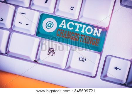 Writing note showing Action Changes Things. Business photo showcasing start doing something against problem resolve or achieve it White pc keyboard with note paper above the white background. stock photo