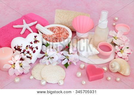Beauty treatment for skincare with ex foliation mineral Himalayan salts, cleansing products and apple blossom flowers on pink background.round. stock photo