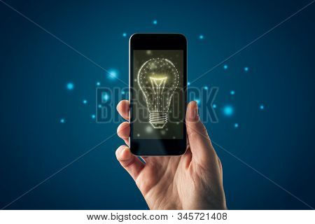 Creative company give you their creativity and ideas. Hands with smart phone and graphics light bulb - symbols of idea, creative thinking, innovations and intelligence. stock photo