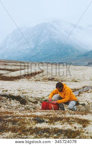 Man hiker packing backpack in mountains travel adventure vacations outdoor trekking active healthy lifestyle Rondane park landscape in Norway stock photo