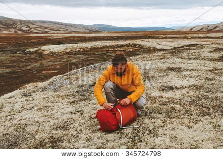 Man hiker packing backpack gear in mountains hiking travel vacations outdoor adventure expedition active healthy lifestyle in Norway moss tundra stock photo