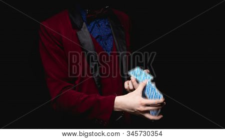 Focus with playing cards in hands of magician, black background close-up stock photo