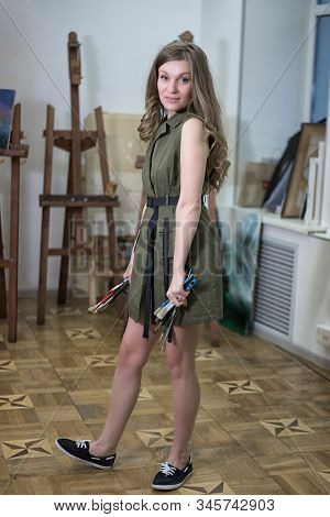 Young attractive woman artist in short dress stands in an art studio holding bunches of brushes in her hands stock photo