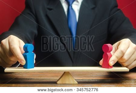 The figure of a man and a woman on scales. Gender pay gap. Equality, inequality. The concept of divorce and division of property. Resolving family disputes. Discrimination stock photo