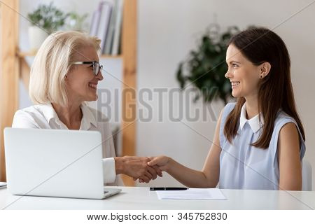 Aged employer congratulates young woman with job interview successful accomplishment stock photo