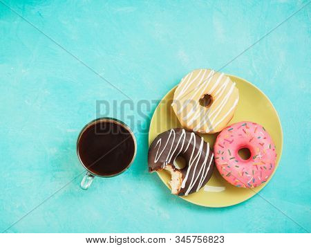 Top view of assorted donuts and coffee on blue concrete background with copy space. Colorful donuts on plate and coffee background. Various glazed doughnuts with sprinkles. stock photo