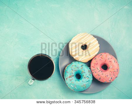 Top view of assorted donuts and coffee on blue concrete background with copy space. Colorful donuts on plate and coffee background. Various glazed doughnuts with sprinkles. Toned image stock photo