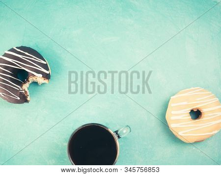 Top view of assorted donuts and coffee on blue concrete background with copy space. Colorful donuts and coffee background. Various glazed doughnuts with sprinkles. Toned image stock photo