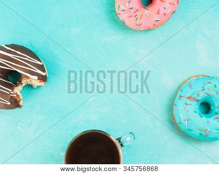 Top view of assorted donuts and coffee on blue concrete background with copy space. Colorful donuts and coffee background. Various glazed doughnuts with sprinkles. stock photo