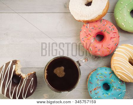 Top view of assorted donuts and coffee on gray wooden background with copy space. Colorful donuts and coffee with copyspace. Various glazed doughnuts with sprinkles on grey wooden table. Toned image stock photo