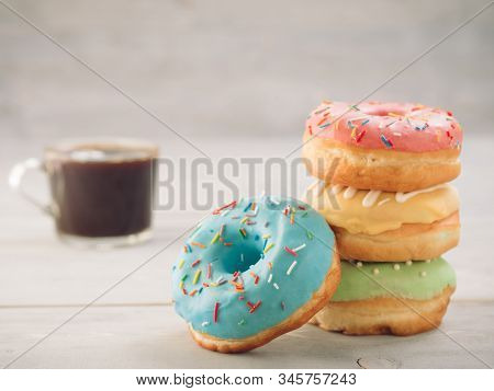 Donuts and coffee on gray wooden table with copy space. Colorful donuts and coffee cup on grey wooden background with copyspace. Glazed doughnuts in stack on foreground and coffee on background stock photo