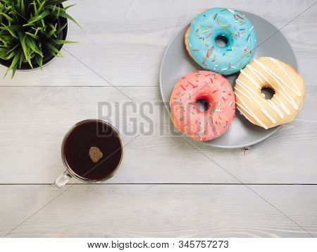 Top view of assorted donuts and coffee on gray wooden background with copy space. Colorful donuts and coffee background with copyspace. Various glazed doughnuts with sprinkles on grey wooden table. stock photo