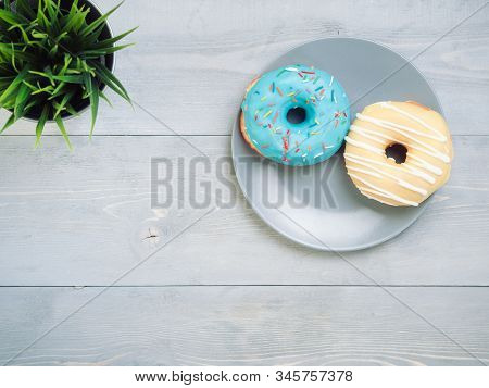Top view of two donuts on gray wooden background with copy space. Colorful donuts on plate with copyspace. Glazed doughnuts with sprinkles on grey wooden table. Smile sign, good morning concept stock photo