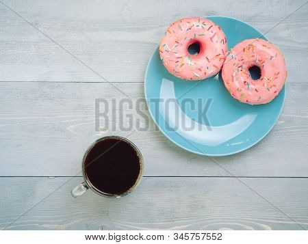 Top view of assorted donuts and coffee on gray wooden background with copy space. Two pink donuts on blue plate and coffee background with copyspace. Smile sign, good morning concept stock photo
