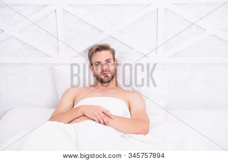 Time to rest. morning erection concept. asleep and awake. Relaxing in bedroom. energy and tiredness. sexy man in bed. pleasant wake up. good morning. nice lazy weekend. stock photo