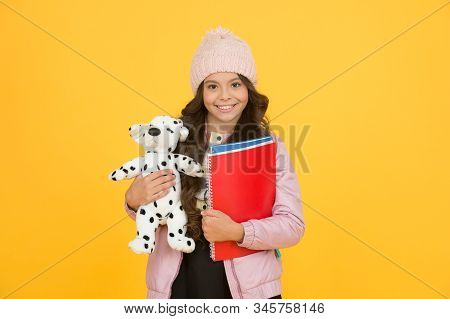 Studying veterinary medicine. Happy child hold toy dog and books. Little girl smile with soft toy. School classes. Toy dog. Learn and play. School and education. Care and treatment of animals. stock photo