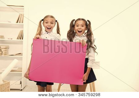 Schoolgirls holding banner announcement. Children greetings copy space. Happy holidays. Congratulations to you. September 1. Congratulations concept. Amazing news. Girls hold congratulations banner. stock photo