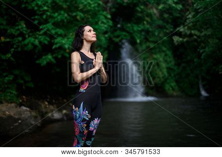 Yoga practice and meditation in nature. Woman practicing near river. stock photo