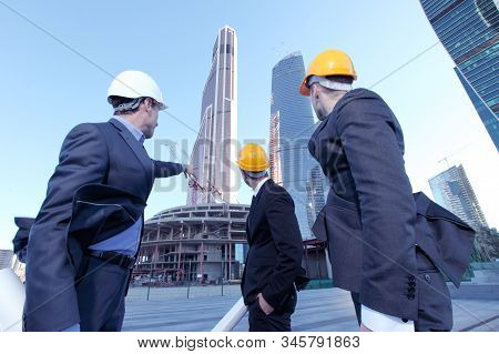 Engineering and architecture concept, engineers working on a building site holding blueprints , architects and engineers inspection in workplace for architectural plan stock photo